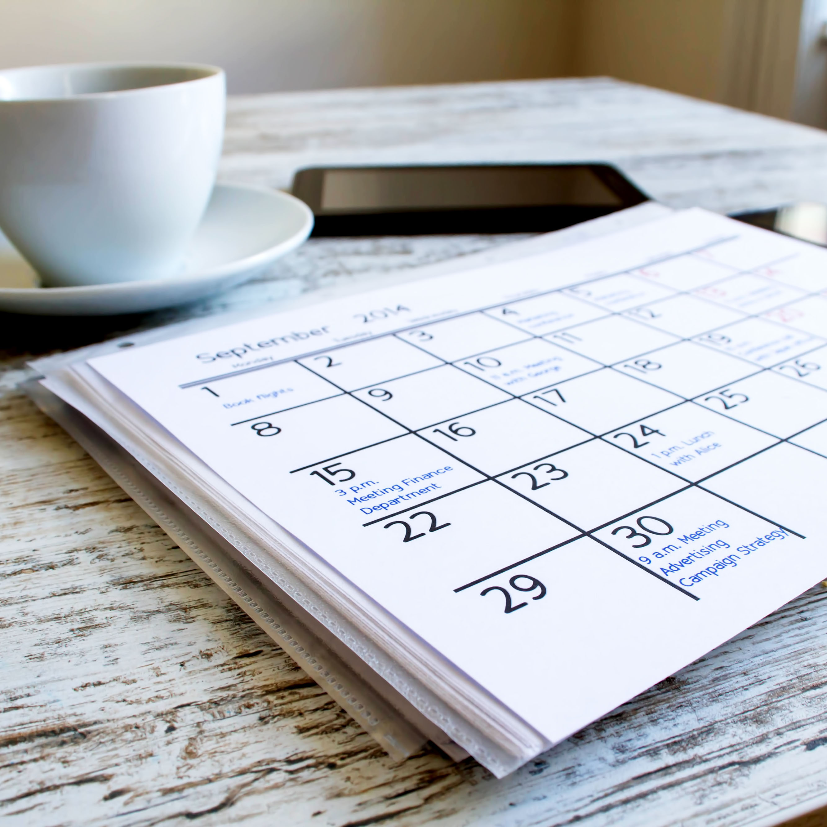 A calendar and cup of coffee